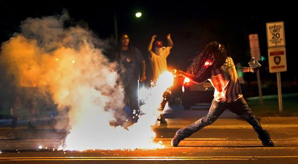 A protestor throws a tear gas canister back at police on Aug. 12. (@kodacohen/Twitter)