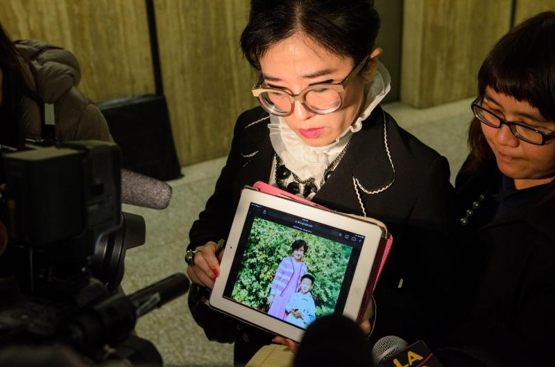 Rose Tsai, attorney for Xinran Ji's family, shows reporters a video of Ji with his family during his childhood in China after a preliminary hearing on 12/12/14 (Benjamin Dunn/Neon Tommy).