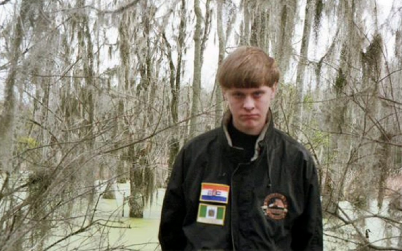 Dylann Storm Roof scowls while wearing a jacket with the flags suggestive of the apartheid-era in South Africa, the other from white-ruled Rhodesia. (Photo via Roof's Facebook)