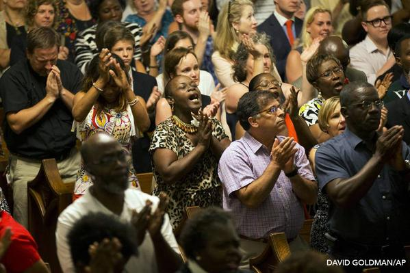 Community members in Charleston, South Carolina come together for a memorial service in response to Wednesday's shooting. ( Photo via David Goldman /Associated Press)