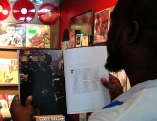 Manager Patrick Washington reads Wax Poetic Magazine. (Celeste Alvarez/Neon Tommy)