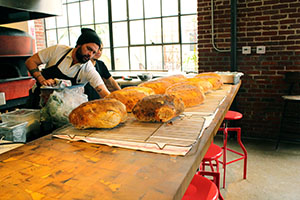 Freshly baked bread lined up in front of Bestia's open kitchen (Kaitlyn Mullin/Neon Tommy)