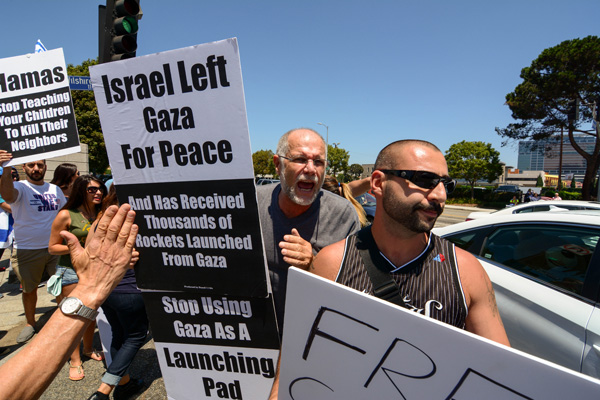 A pro-Israel demonstrator shouts at the Palestinian demonstrator who crossed Wilshire. (Matthew Tinoco/Neon Tommy)