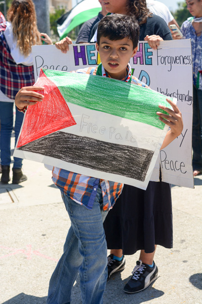 A young boy hold up his crayon colored flag. (Matthew Tinoco/Neon Tommy)