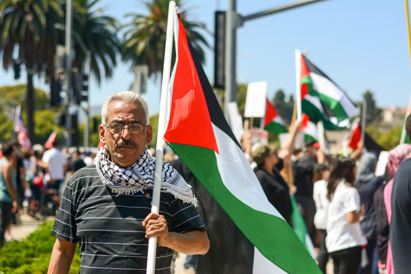 Samir stands resolute with a Palestinian flag. (Matthew Tinoco/Neon Tommy)