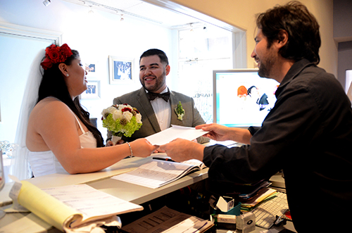 Daniel Franco leads a couple through their oath for their marriage license. (Photo by Hillary Jackson/Neon Tommy.)