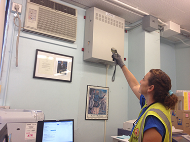 Staff member at Weemes Elementary School fixing one of the school's many broken air conditioning systems. (Shuang Li/Neon Tommy)