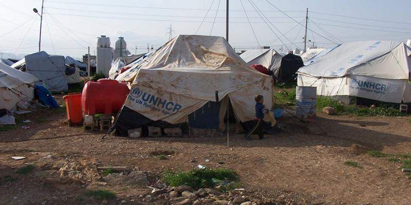 UNHCR tents at a refugee settlement. When applying for refugee status, an applicant can typically wait 15 months to 3 years undergoing a background check. (Wikimedia, Creative Commons)