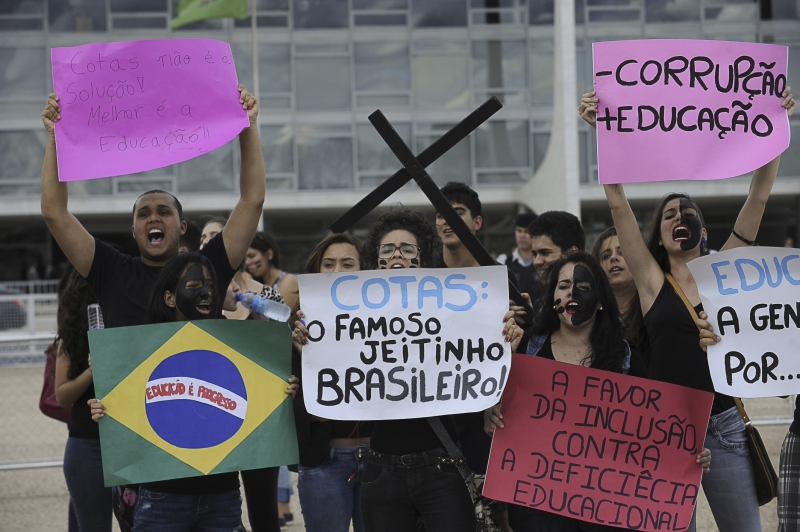 "Demonstrators in Brasilia protest the new affirmative action law with signs reading things like ""Less corruption, more education."" (Agência Brasil)"
