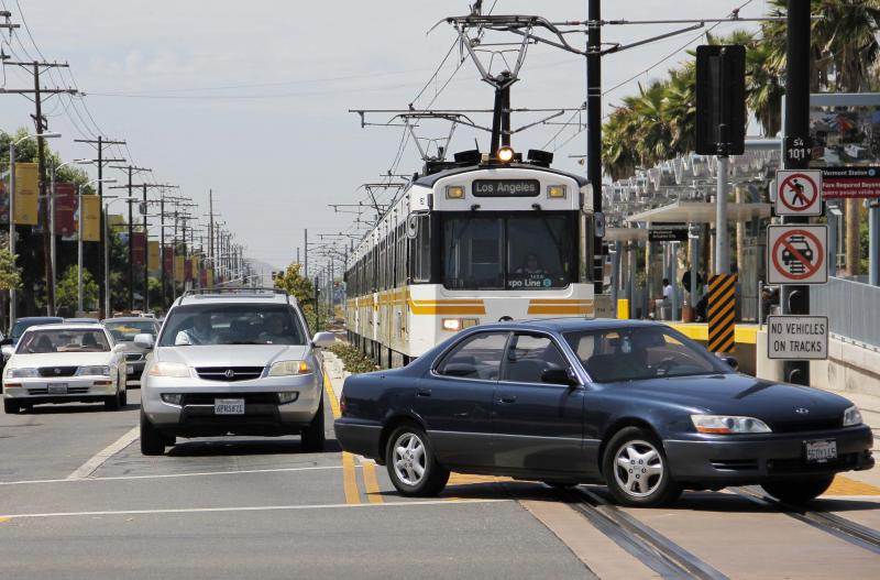 An Expo light-rail train stops and waits as cars turn left. (Rosa Trieu)