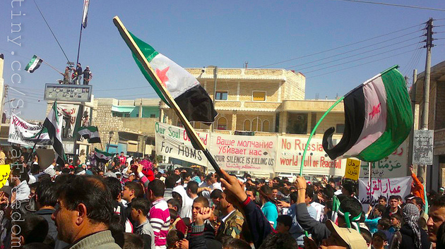 Syrian flags flying over a protest (Courtesy of Creative Commons, FreedomHouse)
