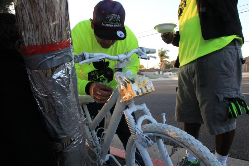 A rider puts a sticker on Benjamin Torres' ghost bike
