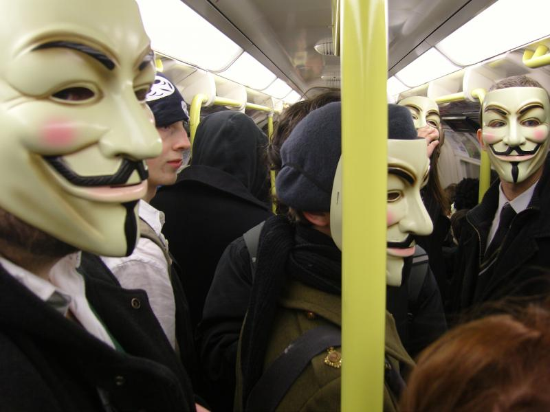 Members of the Anonymous collective ride the train in their trademark masks (James Harrison)